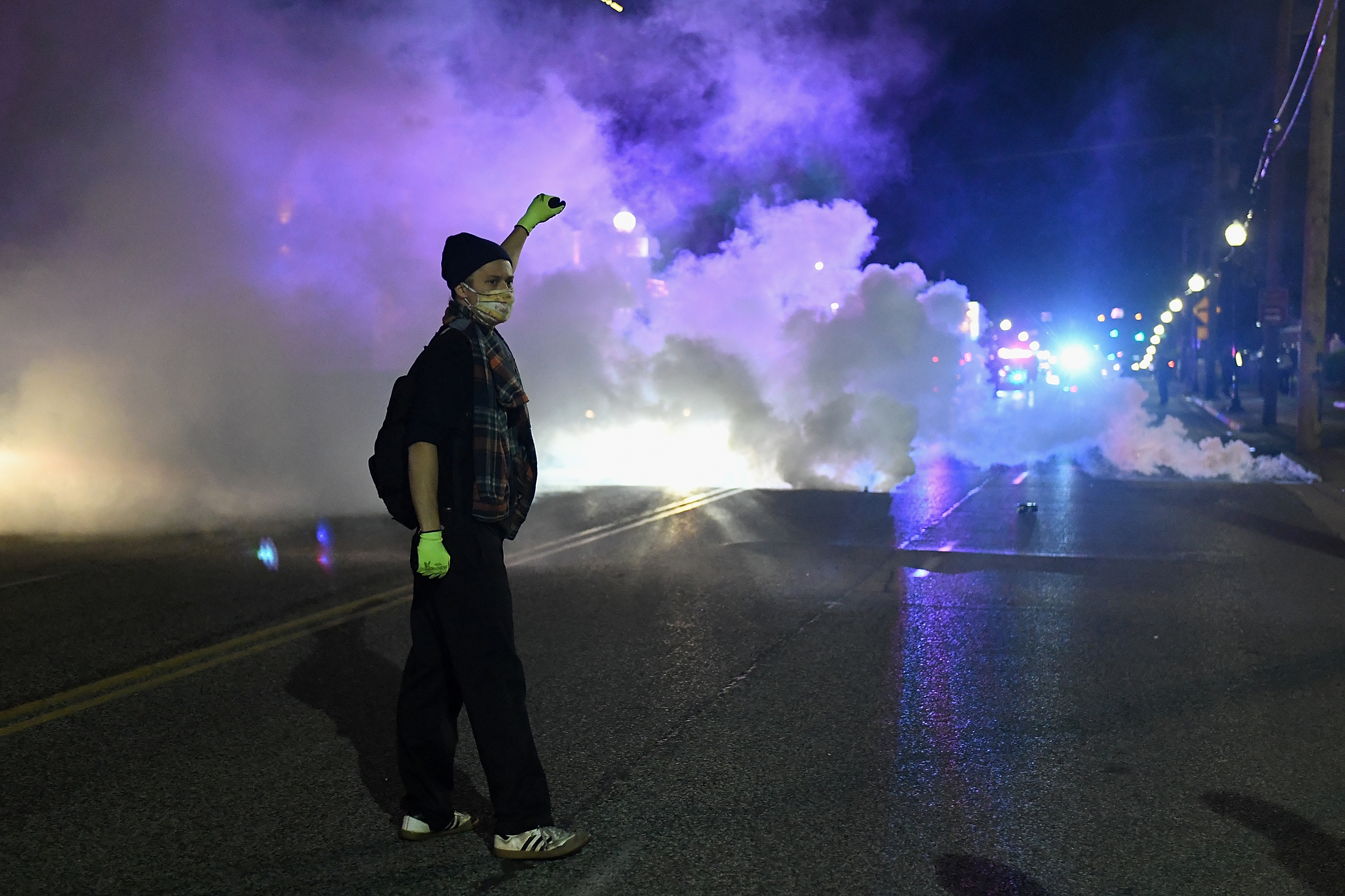 A protester stands amongst tear gas shot by law enforcement to disburse a protest